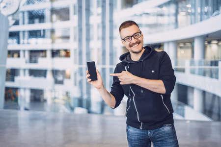 Happy smiling, hipster, glasses, bearded man in jeans show his finger on the black phone Stock Photo