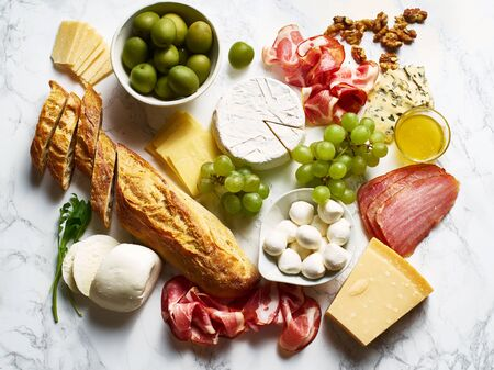 Cheese plate with brie, parmesan, cheddar and meat. Flatlay with variety of gourmet snacks, fruits and baguette on marble board.