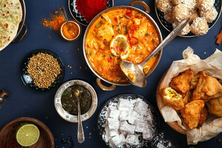 Indian cuisine on diwali holiday: tikka masala, samosa, patties and sweets with mint chutney and spices. Dark blue background, top view.