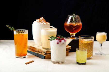 Set of various winter cocktails: mulled wine, eggnog, limoncello, old-fashioned, coconut margarita. Black background, white linen tablecloth.