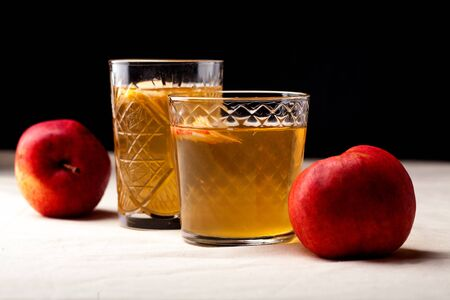 Two vintage glasses with apple cider on black background. Christmas beverages concept. Two red apples and rosemary sprig aside. Warm backlight. Horizontal composition. Side view.