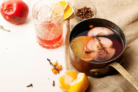 Mulled wine in copper saucepan cooked with slices of orange, apple and thyme. Top view. Linen cloth and tangerines on the table. Scandinavian winter concept.