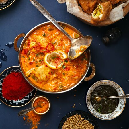 Indian cuisine on diwali holiday: tikka masala, samosa, patties and sweets with mint chutney and spices. Dark blue background. Square composition