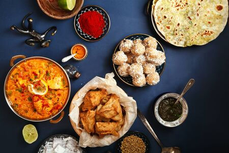 Indian cuisine on diwali holiday: tikka masala, samosa, patties and sweets with mint chutney and spices. Dark blue background