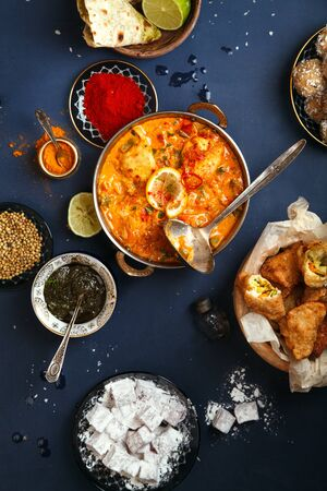 Indian cuisine on diwali holiday: tikka masala, samosa, patties and sweets with mint chutney and spices. Vertical composition. Dark blue background