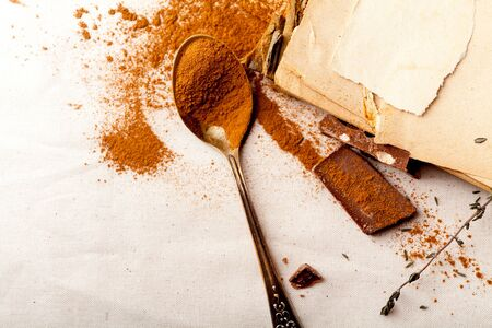 Tea spoon with spilled cocoa powder on linen background with old-fashioned cookbooks aside. Top view. Vintage kitchen concept. Horizontal composition with copy space.
