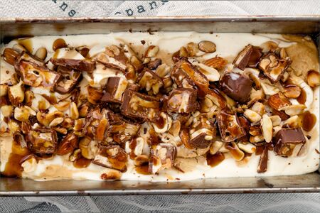 Snickers ice cream with caramel, fried peanuts and hazelnuts in metallic baking tray on rustic background. Gourmet summer treat concept. Close up view Stock Photo