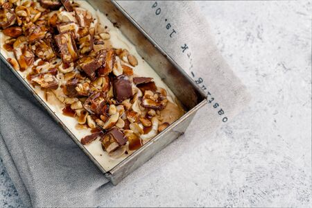 Snickers ice cream with caramel, fried peanuts and hazelnuts in metallic baking tray on rustic background. Gourmet summer treat concept. Composition with copy space.