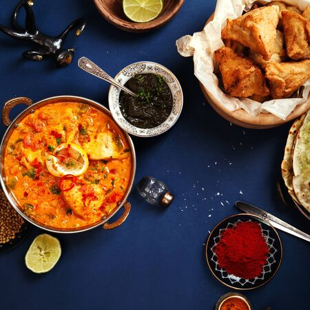 Indian cuisine on diwali holiday: tikka masala, samosa, patties and sweets with mint chutney and spices. Dark blue background. Square composition with copy space