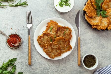 Potato latkes traditional jewish pancakes with sour cream, parsley, dry red pepper flakes and mint sauce. Background, white napkin with blue flowers. Hannukah celebration dish concept.