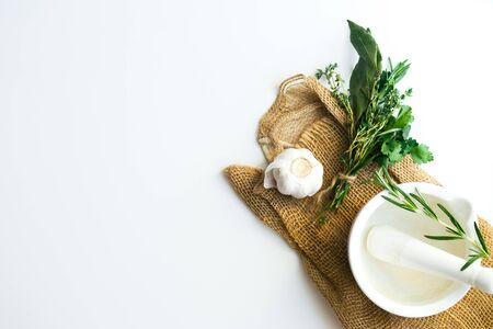 Bouquet garni with bay leaves and fresh herbs de provence on rustic towel on white background with garlic clove and mortar Stock Photo