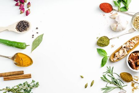 Fresh herbs and dried colorful spices in spoons and bowls arranged in frame on white background with copy space inside 版權商用圖片