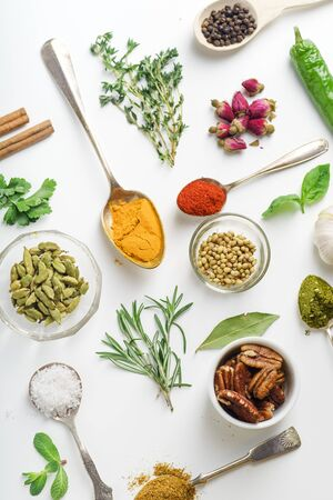 Fresh herbs and dried colorful spices in spoons and bowls arranged geometrically on white background 版權商用圖片