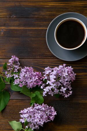 Flatlay with coffee cup and lilac flowers on ol vintage wooden table Imagens