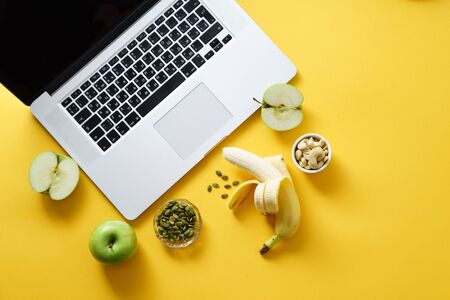 Overhead flatlay image with notebook and healthy snacks on colorful background. Modern lifestyle concept