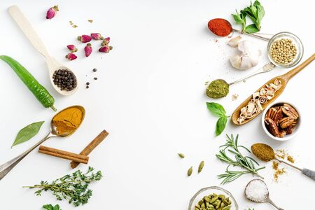 Fresh herbs and dried colorful spices in spoons and bowls arranged on one side with copy space