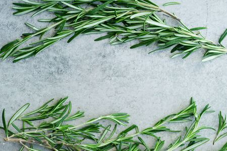 Flatlay with rosemary sprigs arranged on metallic background with text space at the center