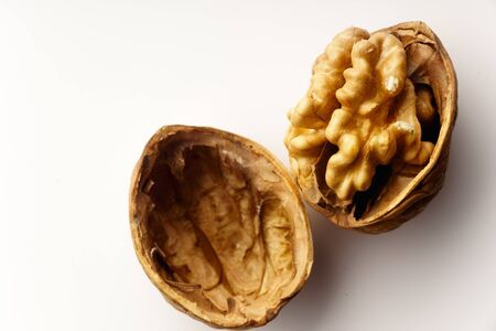 Raw walnuts with cracked nutshells on white background isolated with copy space