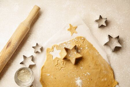 Cooking swedish ginger cookies in a star shape, cutting. Flatlay, overhead composition. Christmas atmosphere
