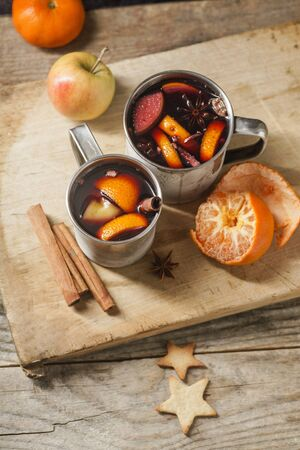 Mulled wine with apple, orange, cardamom, cinnamon, anise and honey. Served in metallic mugs. Wintertime mood.