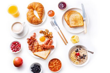 Top view flatlay with varieties of fresh breakfast: fried eggs with bacon and sausages, oatmeal with berries, fried toasts with jam and butter. White background.
