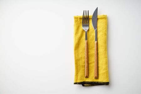 Knife and fork on yellow textile napkin on white background with copy space Imagens
