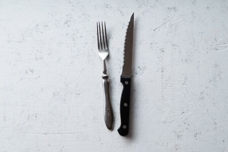Knife and fork on concrete stone background with copy space