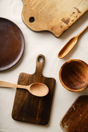 Various wooden tableware. Cutting boards, spoons of different forms, plate and bowl on linen tablecloth