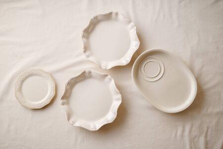Porcelain plates on linen tablecloth. Overhead image, copy space. Natural materials concept. 免版税图像