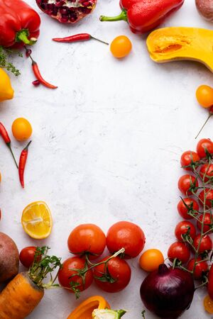 Flatlay with colorful vegetables and copy space arranged on white background. Tomatoes, squash and peppers. Frame shape with space in centre. Vegan nutrition concept