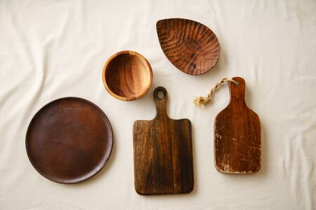Various wooden tableware. Cutting boards, plate and bowl on linen tablecloth
