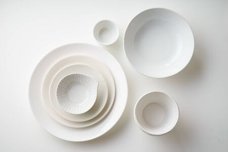 Porcelain plates of various form and size on white background. Overhead image, copy space. 免版税图像
