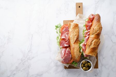 Fresh baguette sandwiches bahn-mi styled. Ham, sliced cheese, tomatoes and fresh lettuce on wooden cutting board on white marble background. Top view, copy space