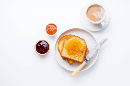 Morning toasts with butter and confiture on white table served with a cup of coffee with milk. Top view, flatlay