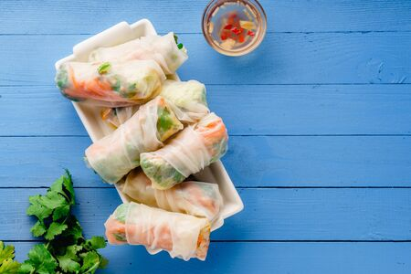 Vegetarian spring rolls with tofu, marinated carrot and daikon and cilantro on blue painted wooden table