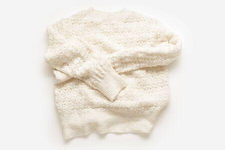 Warm knitted sweater on white background. Minimalistic flatlay