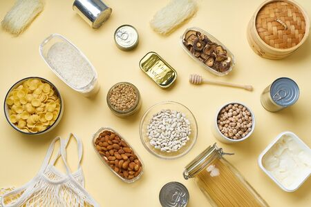 Creative flatlay with pantry staples. Glass jars with pasta, beans and chickpeas, canned goods, nuts and dried mushrooms in reusable containers. Top view pattern with basic products on yellow background Foto de archivo