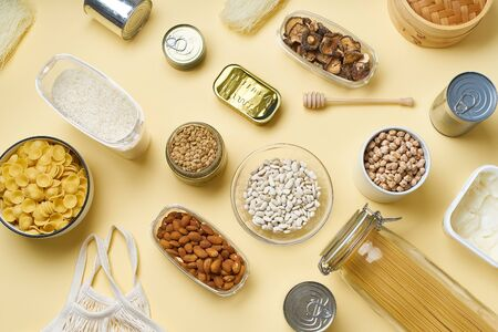 Creative flatlay with pantry staples. Glass jars with pasta, beans and chickpeas, canned goods, nuts and dried mushrooms in reusable containers. Top view pattern with basic products on yellow background