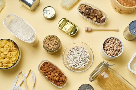 Creative flatlay with pantry staples. Glass jars with pasta, beans and chickpeas, canned goods, nuts and dried mushrooms. Top view pattern with basic products on yellow background