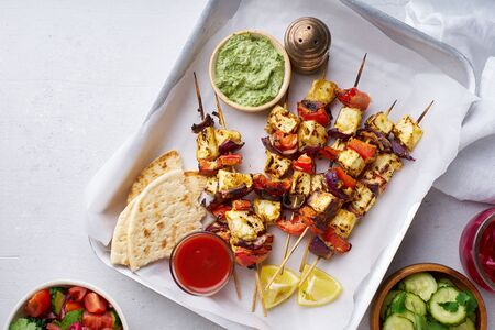 Paneer tikka starter kebabs with mint chutney and chapati. Traditional indian cuisine, grilled cheese skewers with onion and bell pepper slices. Vegetarian dish marinated in tikka sauce.