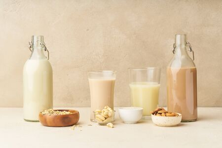 Dairy alternative. Rice, oat, cashew and chocolate almond milk in bottles and glasses on beige background. Healthy protein vegan drink. Imagens
