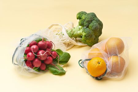 Zero waste food shopping with reusable bags. Flat lay with fruits and vegetables in textile packaging. Broccoli, radishes and oranges on yellow background.