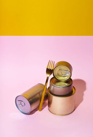 Non-perishable canned goods on pink background. Pandemic kit staple. Food food staples prepared to survive Coronavirus COVID 19 pandemic at the time of quarantine and home isolation