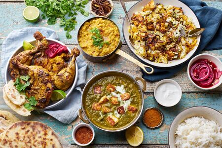 Indian cuisine dinner: tandoori chicken, biryani, red lentil curry dal with rice naan, palak paneer and basmati rice on wooden background