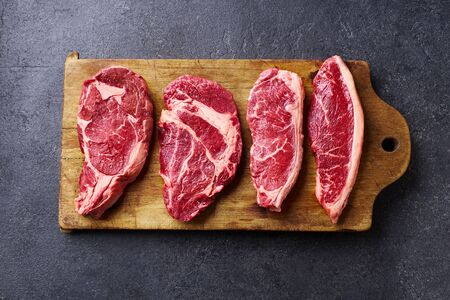 Variety of fresh Black Angus Prime raw beef steakes: ribeye, striploin, chuck roll and picanha on wooden cutiing board