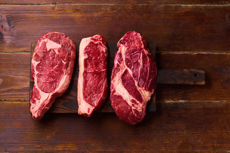 Variety of fresh Black Angus Prime raw beef steakes: ribeye, striploin and picanha on cutiing board wooden background copy space top view Banco de Imagens