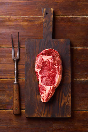Flat lay Black Angus prime beef chuck roll steak on cutting board wooden background copy space. Flat lay cooking ingredient