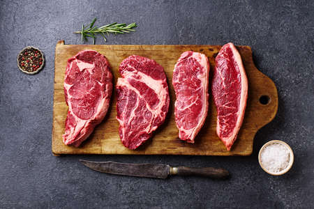 Variety of fresh Black Angus Prime raw beef steakes: ribeye, striploin, chuck roll and picanha on wooden cutiing board Banco de Imagens