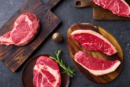 Top view variety of fresh Black Angus Prime raw beef steakes: ribeye, striploin, chuck roll and picanha on cutiing boards Banco de Imagens