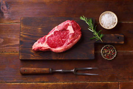 Flat lay Black Angus prime beef rib eye steak with rosemary, salt and pepper on cutting board wooden background copy space